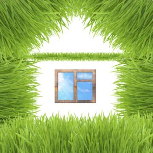 Conceptual green grass house isolated on white