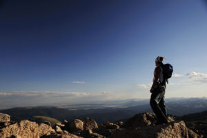 Man stands alone on top of a mountain