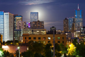 An eerie glowing full moon rises behind a tall skyscraper in the Denver Colorado skyline.