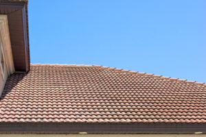 Peak of a clay tile roof with half round shingles against a blue sky in southern florida