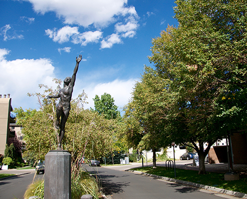 Tree lined street with statue in Cherry Creek Country Club Denver.