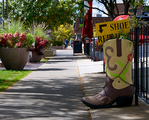 Boot shaped shoe shop sign on Cherry Creek sidewalk.