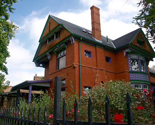 Large historic multi story brick home with hedges in City Park Denver.