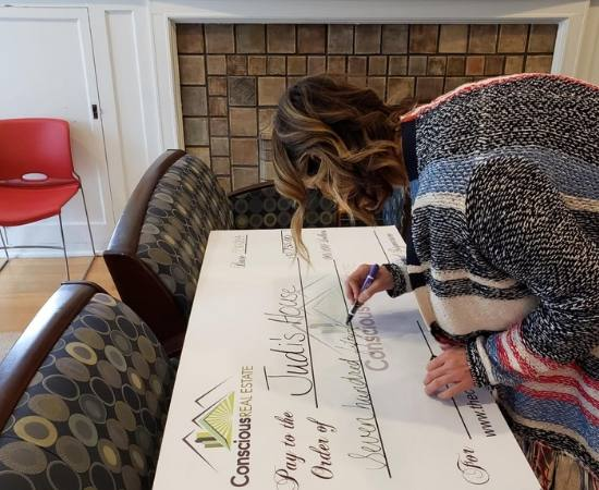 Conscious Real Estate Owner and Founder Allison Parks writes out a donation check.