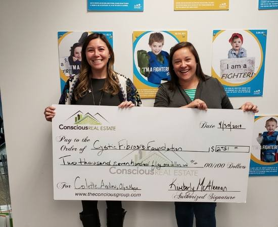 Realtor Kimberly McAleenan presents a check to the Cystic Fibrosis Foundation through Conscious Real Estate's giving program.